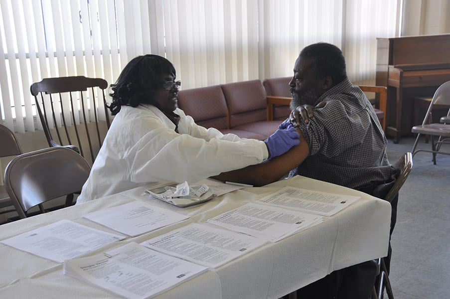 Clinician administering vaccination on Rose Centers participant's arm