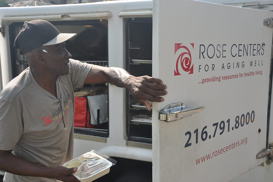 Rose Centers Home-Delivered Meals driver/jumper taking a meal out of the truck