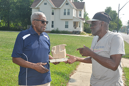 Home-Delivered Meals- A Rose Centers for Aging Well jumper delivering a meal to a home-delivered meals participant